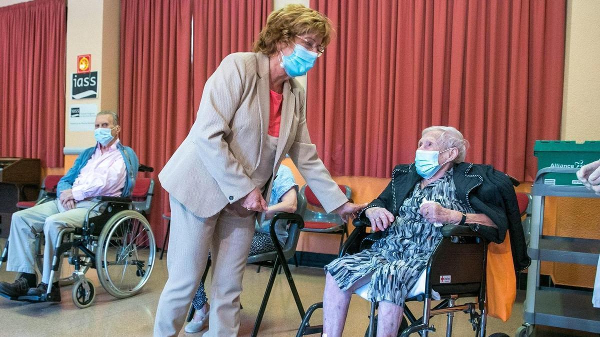 La consejera de Ciudadanía y Derechos Sociales del Gobierno de Aragón, María Víctoria Broto, saluda este lunes de una anciana que ha recibido esta mañana su tercera dosis de la vacuna contra la covid-19 en Zaragoza.