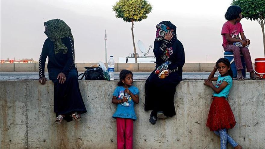 Una familia de refugiados sirios espera sentada cerca a la frontera entre Siria y Turquía en Akcakale, provincia de Sanliurfa (Turquía). / EFE