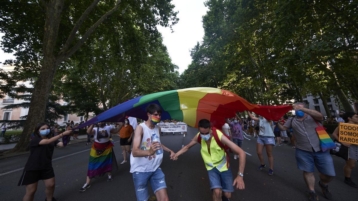 Dos personas cogidas de la mano bajo una bandera LGTBI en la manifestación.