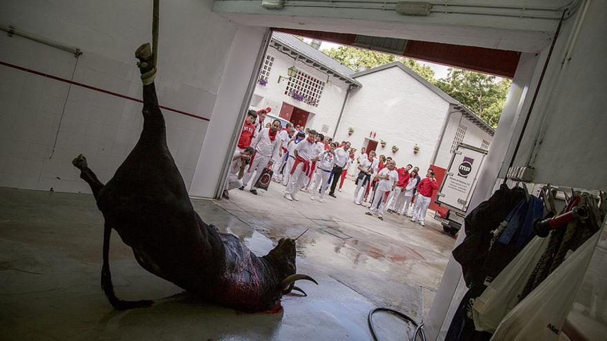 Decenas de personas observan a uno de los toros matados en las fiestas de San Fermín./ @Tras_los_Muros.