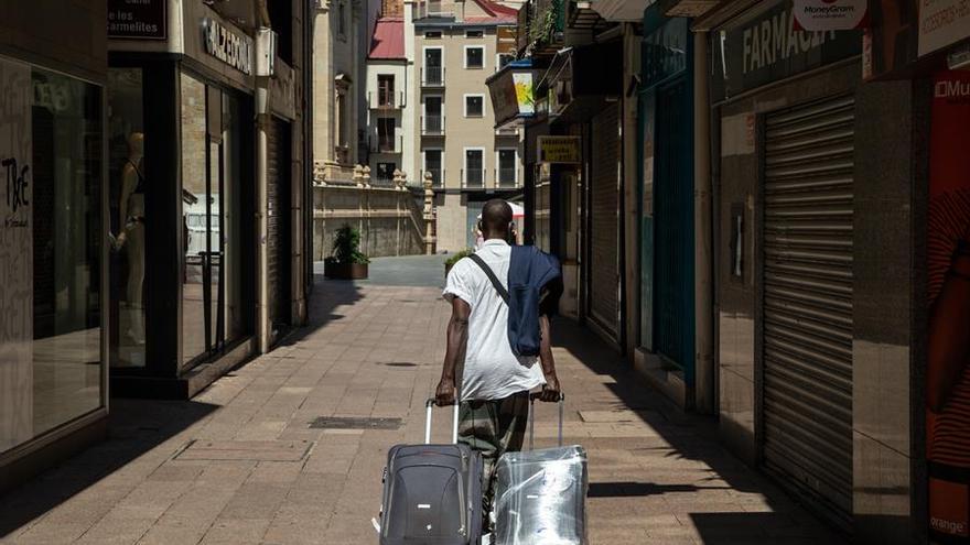 Una persona camina por una calle con maletas
