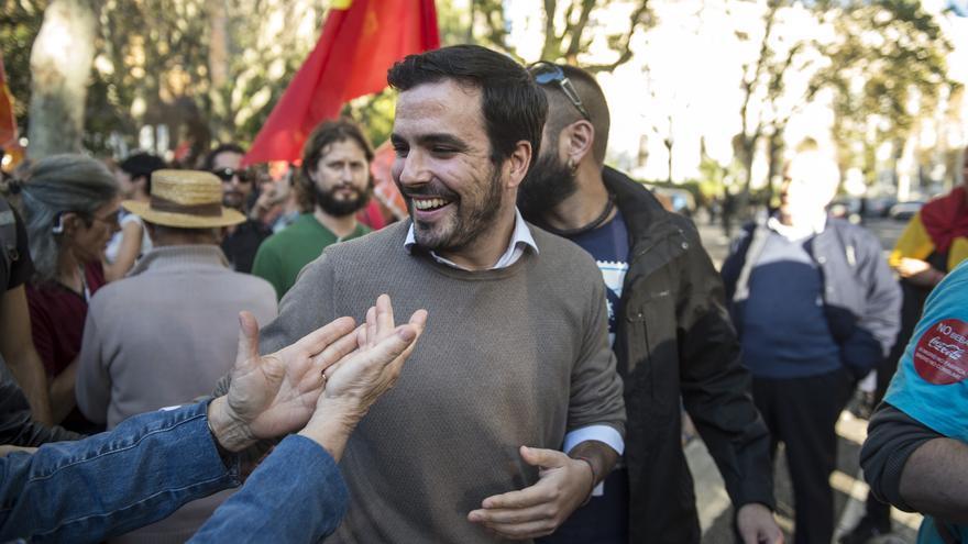 El diputado de Unidos Podemos, Alberto Garzón, saluda a los manifestantes que abarrotan el Paseo del Prado, minutos antes de dar comienzo el pleno