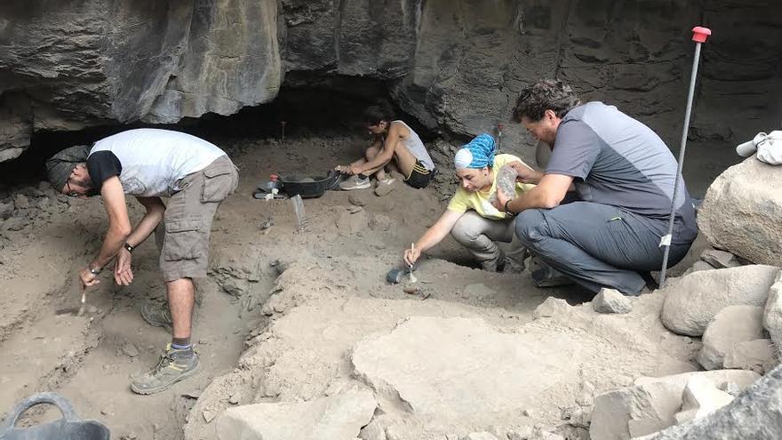 Los directores del campus junto a dos alumnas en las labores de excavación.