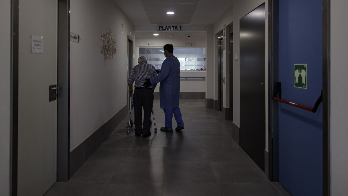 Un trabajador atiende a un anciano en una residencia de mayores