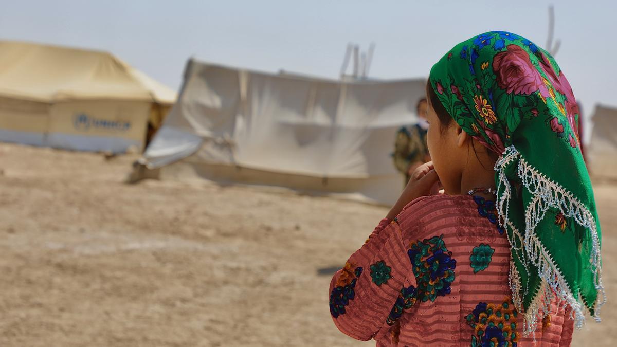 La niña de 9 años Nazeela observa a los mayores charlar en un campamento en Afganistán.