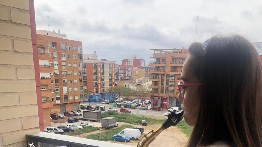 Una joven música intepreta 'Paquito el Chocolatero' desde su balcón en València