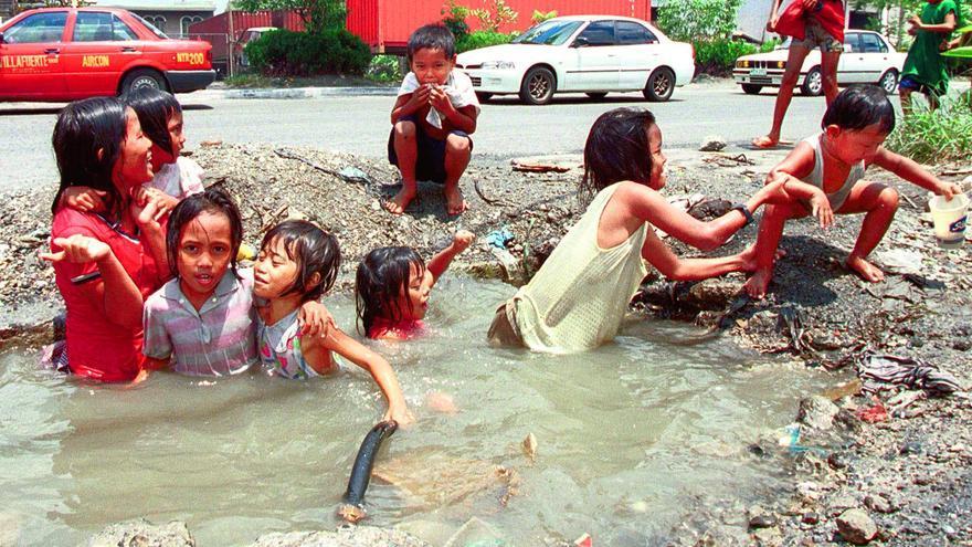 Un grupo de niños se refresca del calor del verano sumergiéndose en una tubería de agua reventada en Manila