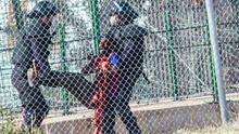 Dos agentes devuelven a un inmigrante a Marruecos tras el intento de salto del 1 de mayo./ Foto:José Palazón.