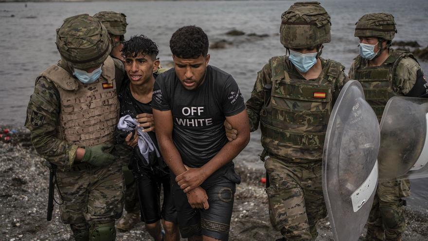 Jóvenes marroquíes llegados a nado a Ceuta, escoltados por soldados españoles.