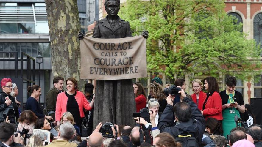 Varias personas se fotografían junto a la estatua de la líder británica del movimiento sufragista Millicent Fawcett ante el Parlamento británico.