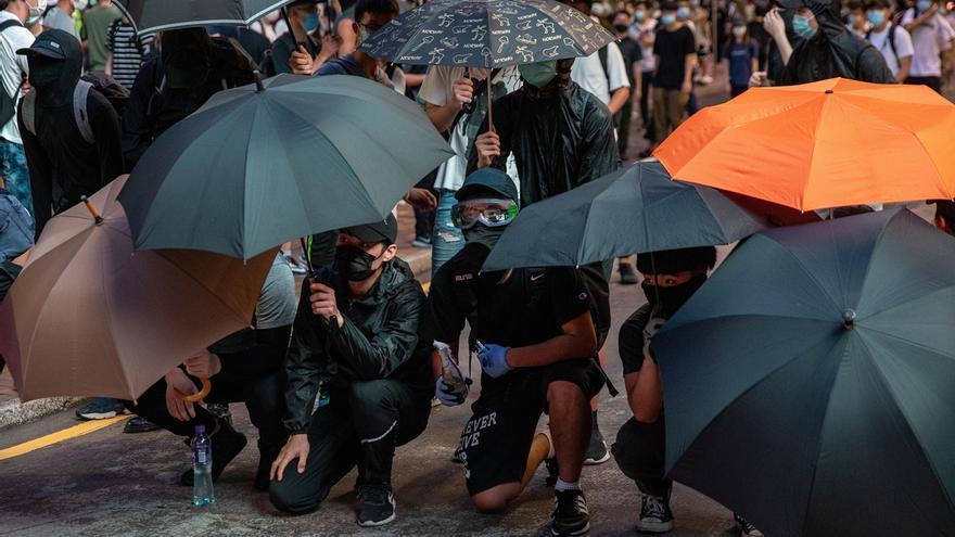 Un manifestante sostiene una bomba incendiaria, (C), durante una manifestación contra la ley de seguridad nacional en Hong Kong, China.
