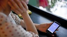 Una joven accede a una red social desde el móvil.