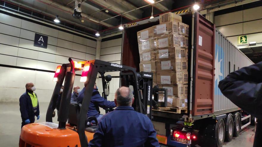 Operarios descargan material sanitario adquirido en China que llegó en avión al aeropuerto de Zaragoza.