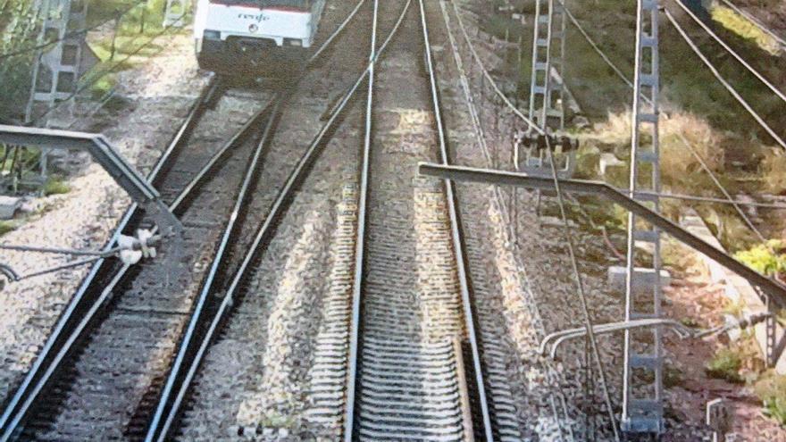 Un tren de cercanías circula por la red ferroviaria mientras el tercer rail habilitado finaliza al llegar a un cruce