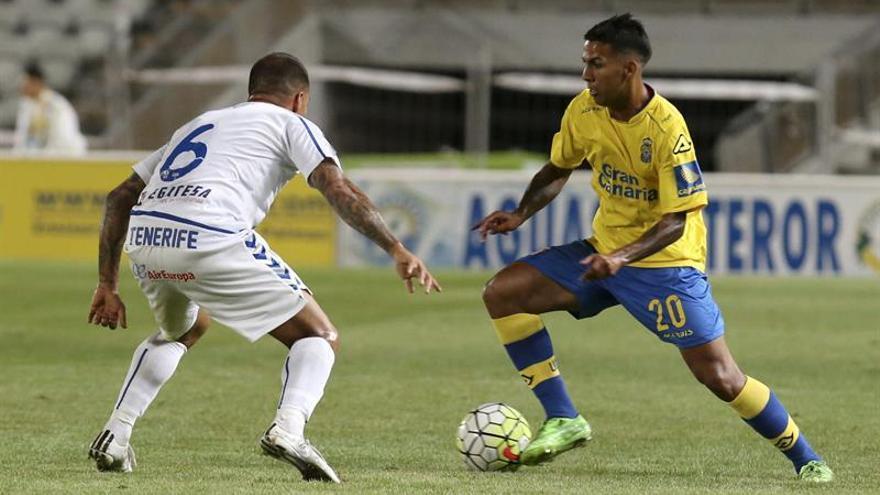 El centrocampista de la U. D. Las Palmas, Jonathan Viera (d), intenta superar al jugador del C. D. Tenerife Vitolo durante el encuentro amistoso que han disputado en el Estadio de Gran Canaria. (EFE/Elvira Urquijo A)
