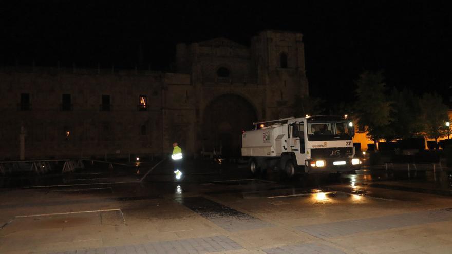 Un operario de limpieza del Ayuntamiento de León borra los nombres escritos durante el día / Israel Salcedo