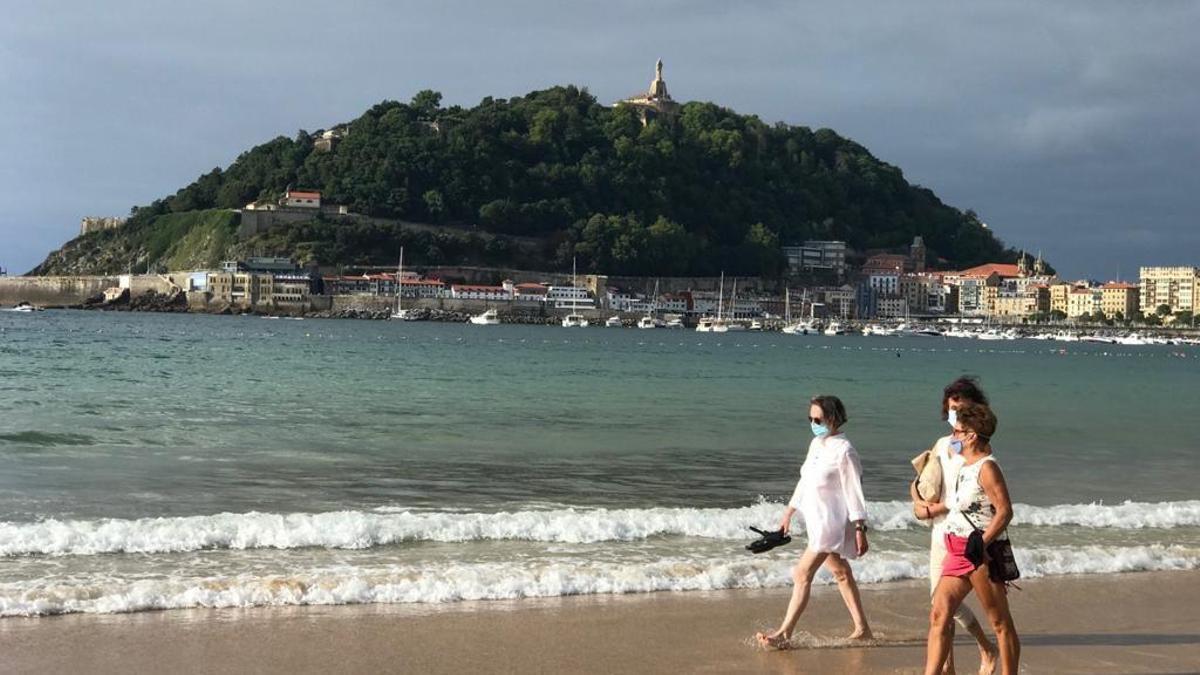 Tres mujeres, con mascarilla, pasean este jueves por la playa de la Concha de Donostia
