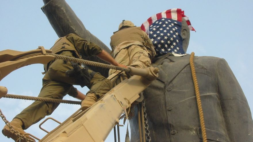 Tropas estadounidenses colocando la bandera de EEUU en una estatua de Sadam Hussein (Bagdad, 9 de abril 2003).