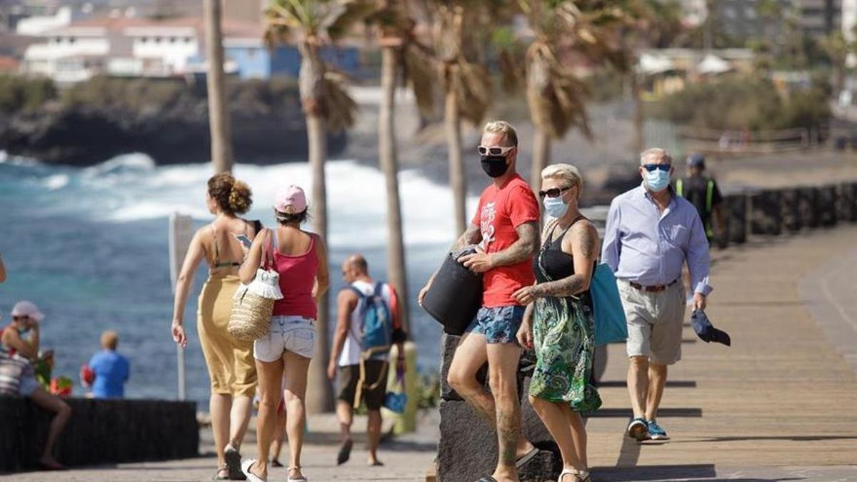 Unos bañistas se disponen a entrar en una playa de la localidad de Las Caletillas, en el municipio de Candelaria, Tenerife