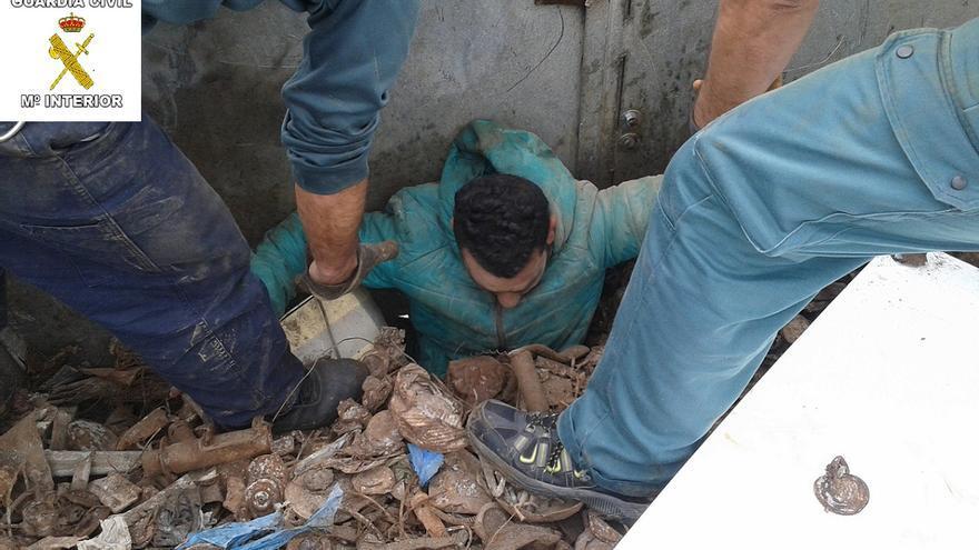 Un migrante es sacado del camión de la chatarra en Melilla   Foto: Guardia Civil