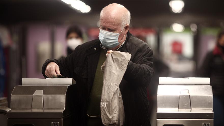 Una anciano en los torniquetes del metro de Madrid.