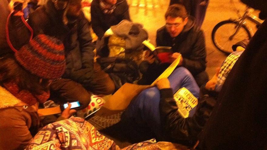 Parte de las personas acampadas escuchan como otra lee 'Las venas abiertas de América Latina', de Eduardo Galeano, después de que la Policía Municipal les obligase a cambiar de sitio para limpiar la plaza / H.J.