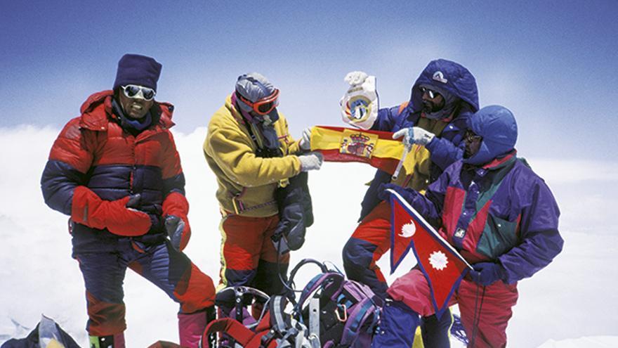 """En la cima del """"Techo del Mundo"""", dos miembros del GMAM sostienen la bandera  de España, entre Lakpa y Pemba Norbu, que portan la de Nepal."""
