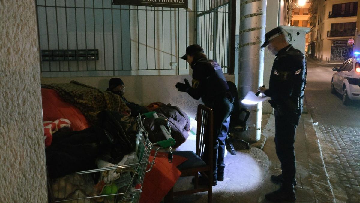 Dos agentes atienden a un sin techo en València.