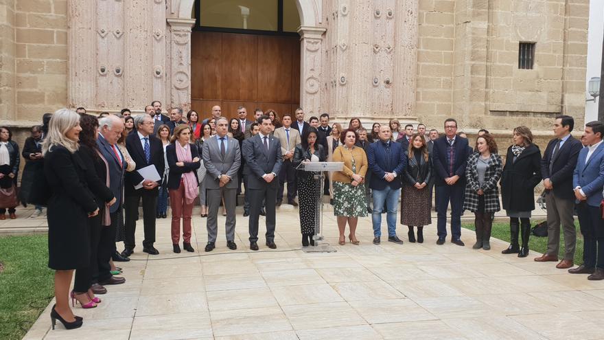 La presidenta del Parlamento, Marta Bosquet, lee un manifiesto consensuado por todos los grupos, menos Vox, de condena a la violencia machista a las puertas del salón de Plenos, en presencia de los miembros del Gobierno andaluz y diputados de PSOE, PP, Ciudadanos y Adelante Andalucía.