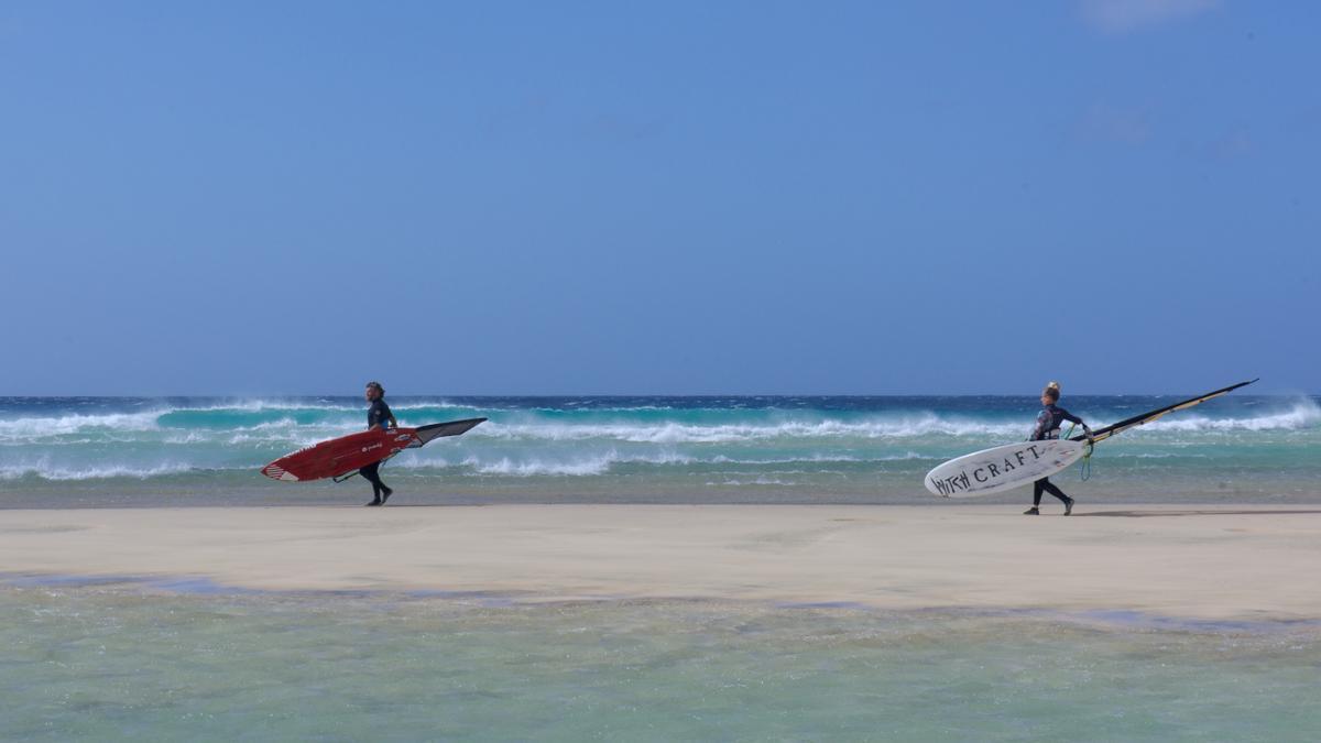 Dos personas se disponen a hacer windsurf en la playa del Risco del Paso, en Fuerteventura