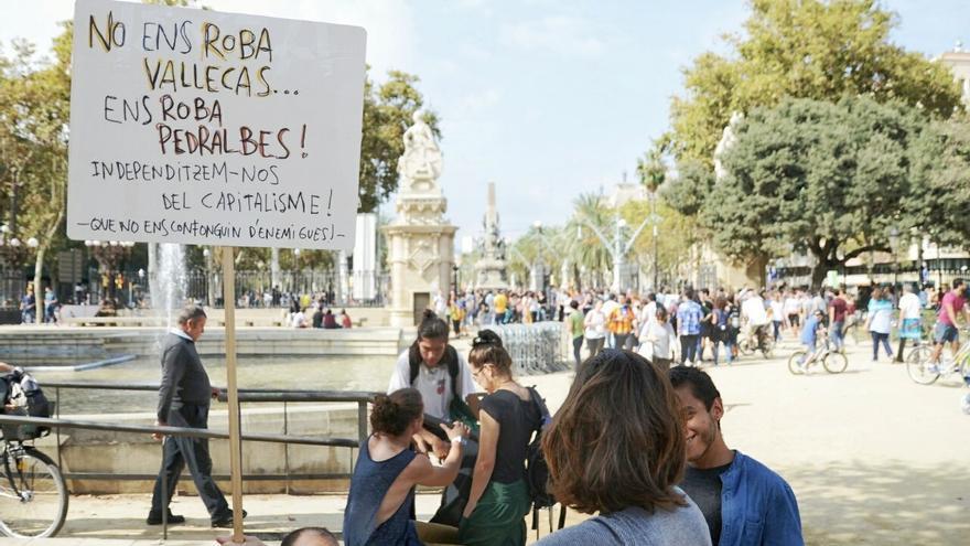 Manifestantes con un cartel que dice: 'No ens roba Vallecas, ens roba Pedralbes'
