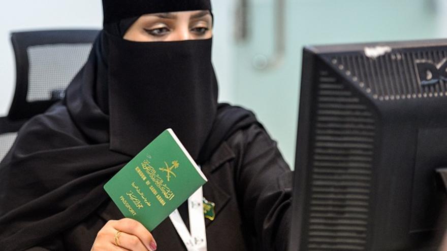 """Una empleada del servicio de Inmigración y Pasaportes comprueba la identidad de una persona.  Arabia Saudita ha aliviado las restricciones de viaje para las mujeres, permitiendo que las mayores de 21 años obtengan pasaportes sin solicitar el aprobación de sus """"tutores""""."""