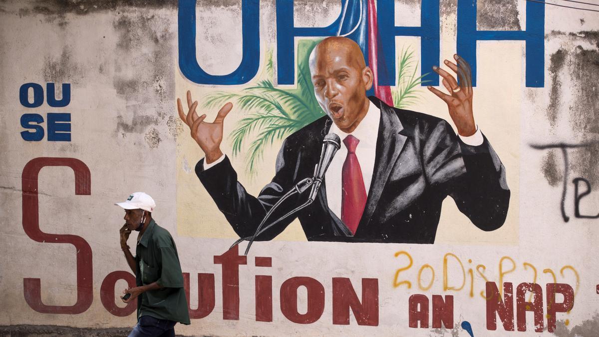 Un hombre camina junto a un mural en homenaje al asesinado expresidente Jovenel Moise, en Puerto Príncipe.