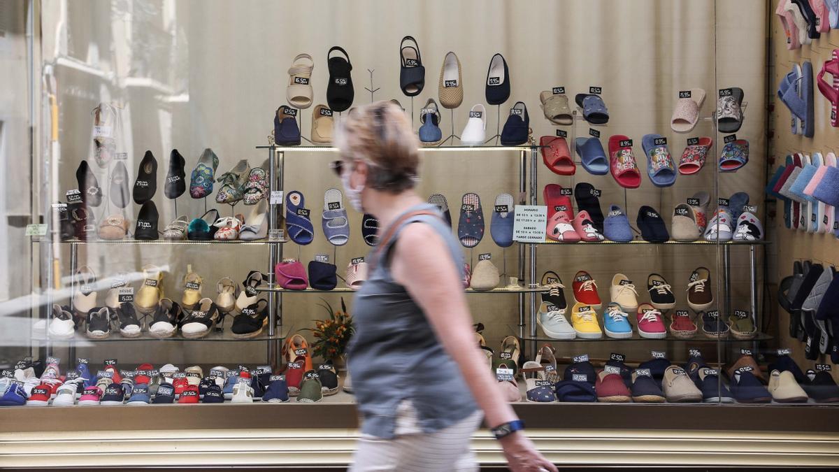 Una mujer observa el escaparate de una zapatería