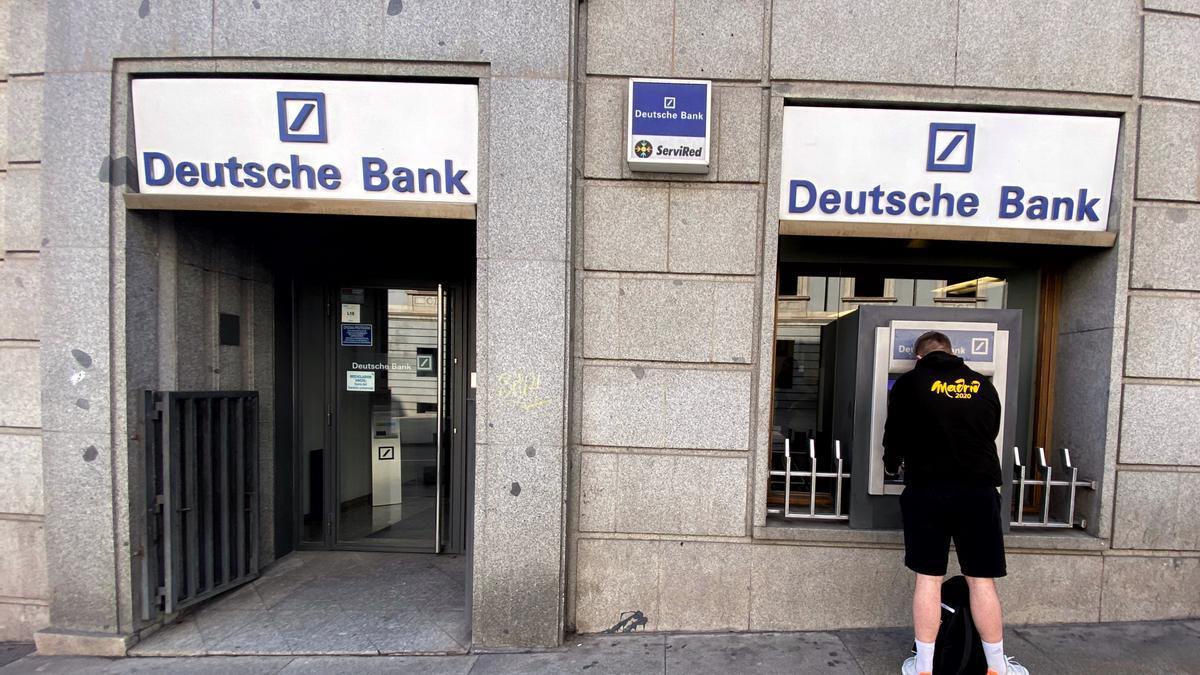 Un hombre retira dinero de un cajero Deutsche Bank, en Madrid (España), a 7 de febrero de 2020.