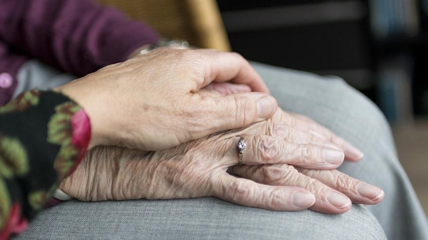 Imagen de archivo de las manos de dos personas mayores.