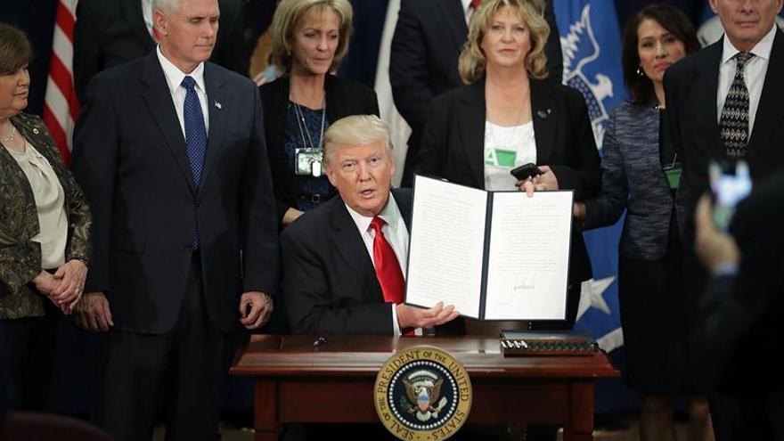 El presidente estadounidense, Donald J. Trump (c), muestra la orden ejecutiva para destinar fondos federales a la construcción del muro en la frontera con México durante una ceremonia en el Departamento de Seguridad Nacional en Washington, este 25 de enero de 2017.