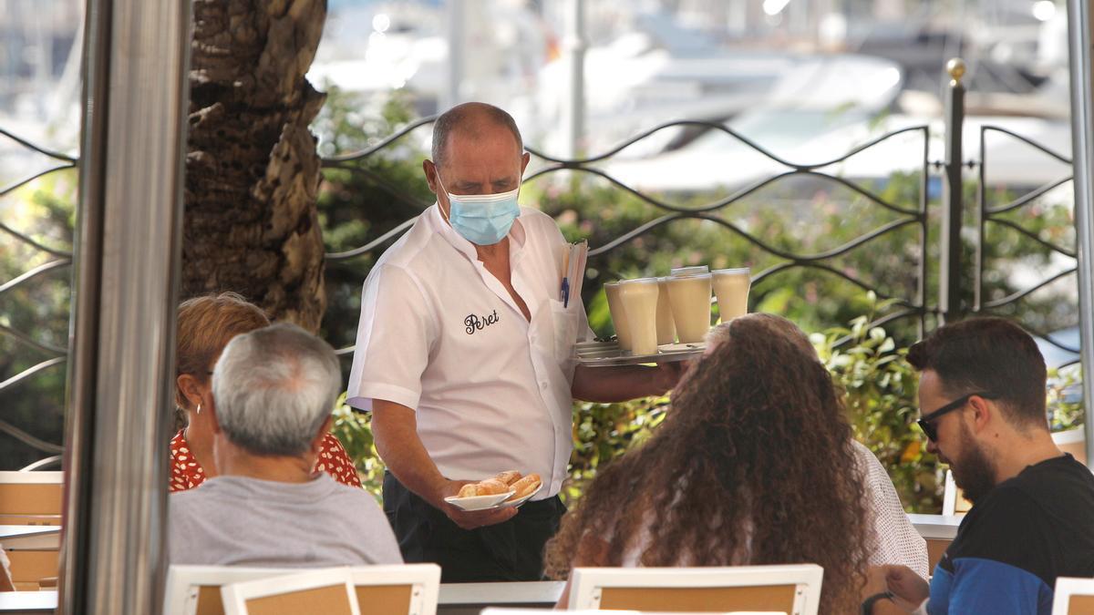 Un camarero sirve una mesa en una terraza de la Explanada de Alicante.