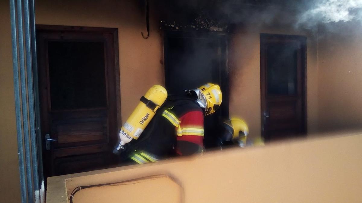 Un bombero durante las tareas de extinción del incendio registrado en la tarde de este jueves en un cuarto de lavadora de un edificio de Los Llanos de Aridane.
