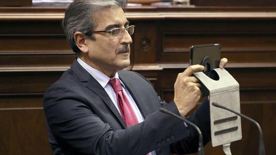 El diputado Román Rodríguez hace unas fotografías a los escaños vacíos antes de comenzar su intervención en el último debate sobre el estado de la nacionalidad de la legislatura. EFE/Cristóbal García