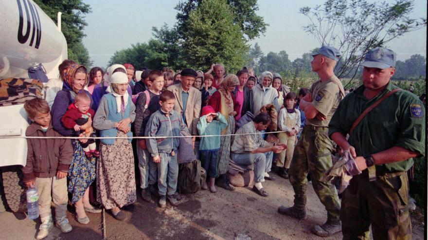 Varios refugiados esperan ante un punto de ayuda médica vigilado por soldados de la ONU en Tuzla (Bosnia), en 1995.