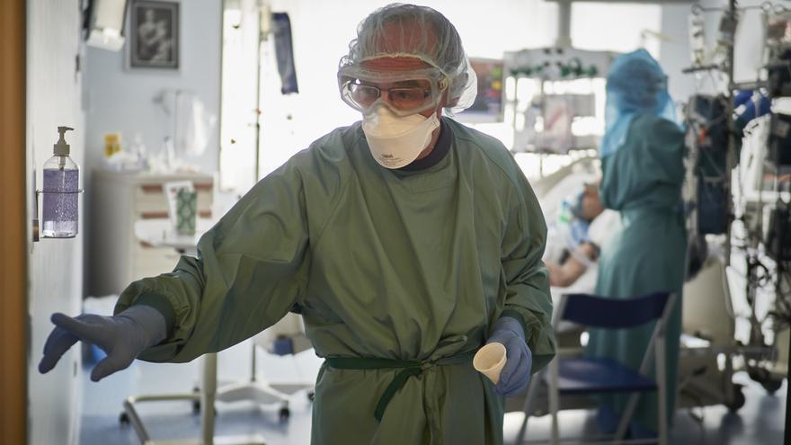 Un trabajador sanitario totalmente protegido sale de una habitación de la UCI de la Clínica Universidad de Navarra, en Pamplona