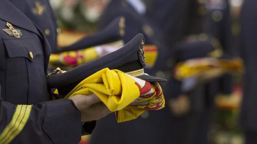 Compañeros de los cuatro militares fallecidos el pasado 19 de marzo, pertenecientes al escuadrón 802 del Escuadrón del Servicio Aéreo de Rescate (SAR) portan las gorras, condecoraciones y banderas que cubrían los féretros, para ser entregados a sus familiares, en el funeral celebrado en la Base Aérea de Gando, en Gran Canaria . EFE/Ángel Medina G.