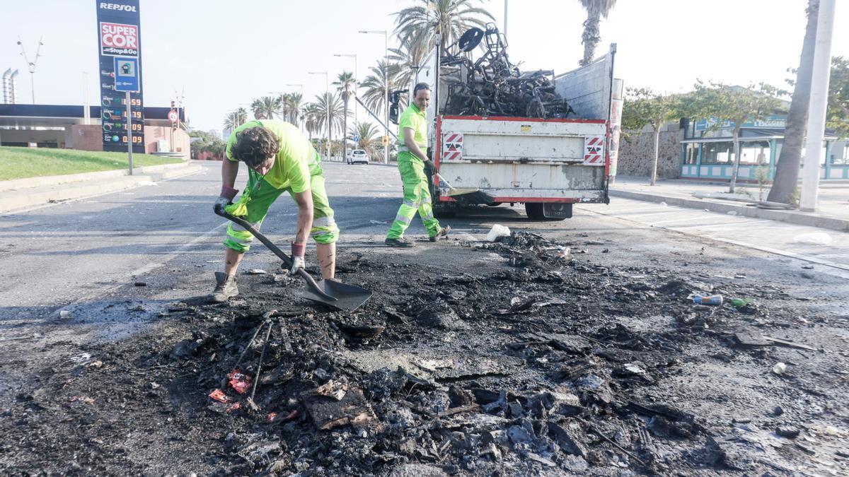 Miembros del servicio de limpieza trabajan tras los incidentes registrados el sábado por un botellón en las playas de Barcelona