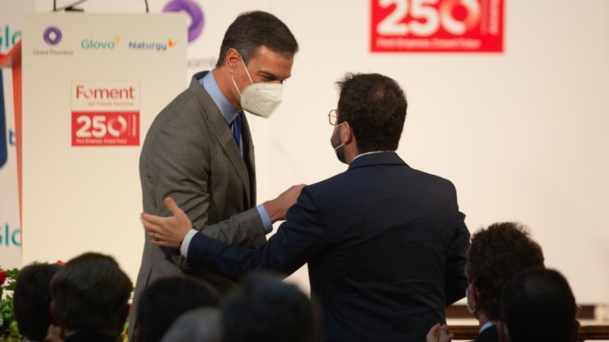 El presidente del Gobierno, Pedro Sánchez (i) y el president de la Generalitat, Pere Aragonés (d), se saludan durante la entrega de la medalla del 250 aniversario de Foment del Treball al editor de 'La Vanguardia', Javier Godó. ARCHIVO.