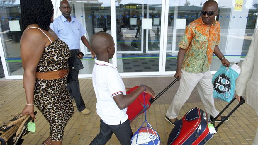Llegada del niño Adou, junto a su madre y su padre (izq), en el aeropuerto de Fuerteventura. (EFE/Carlos De Saá)