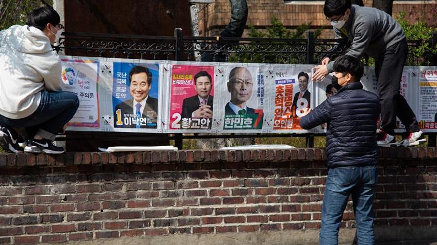 Seguidores de diversos partidos colocan posters de lo canditatos en plena campaña para las elecciones generales del próximo 15 de abril en Corea del Sur, coincidiendo con la pandemia de Covid-19 que supera los 10 mil contagios.