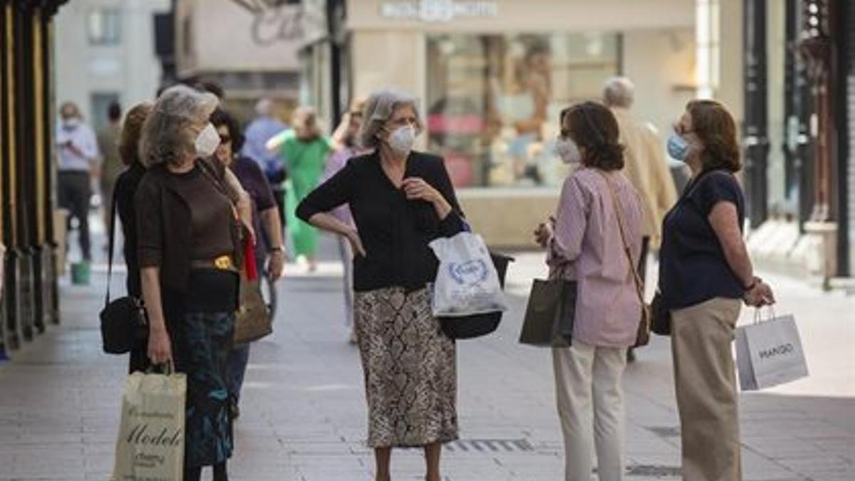 Un grupo de mujeres, en la calle con mascarilla.