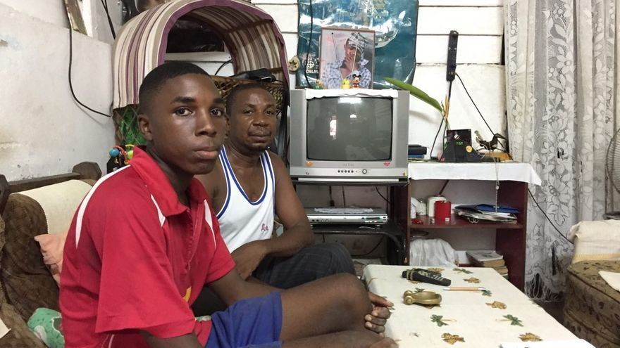 El padre de Bikai junto a su hijo pequeño en el salón de su casa. La foto de su hijo fallecido en el Tarajal continúa sobre su televisión.