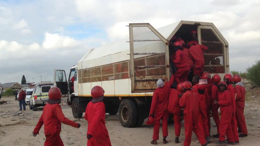 Los Hormigas Rojas en una misión de limpieza de un asentamiento chabolista en Khayelitsha, Ciudad del Cabo.